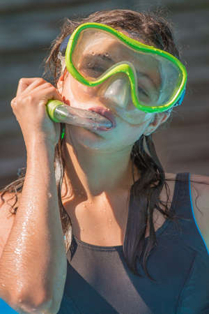 cute young girl wincing with yellow diving mask and snorkel Stock Photo