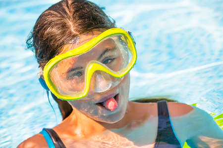 wincing: Portrait of young wincing girl in the water with yellow diving mask on her head Stock Photo