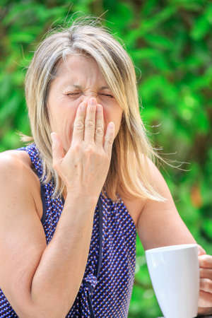 antihistamine: woman drinking her tea and sneezing due to allergic with green background