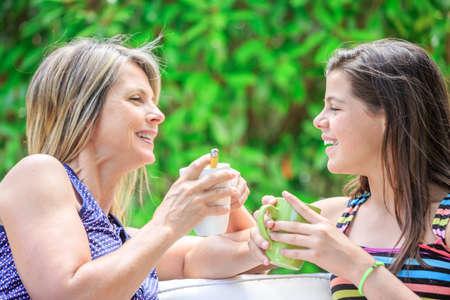 personas abrazadas: madre e hija están relajando en casa beber té