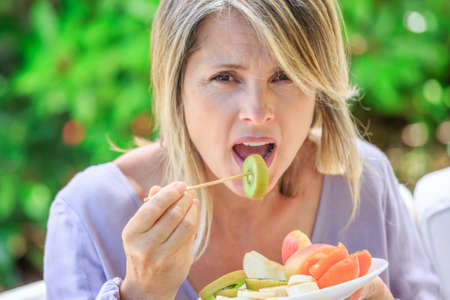 eating fruits: attractive blond woman eating fresh fruits Stock Photo