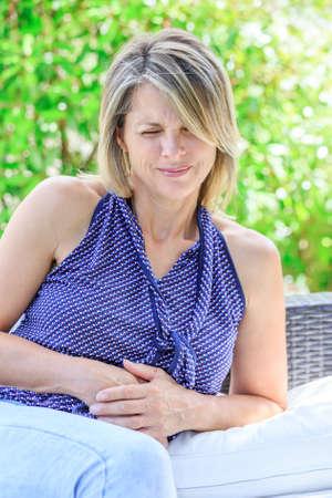 convulsion: mujer con dolor de vientre aislado en un fondo verde