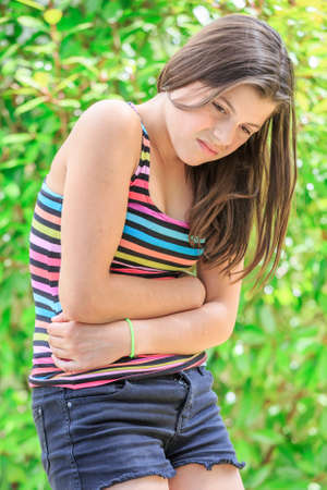 bellyache: young girl with bellyache isolated on a green background