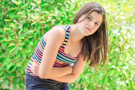 convulsión: chica joven con dolor de estómago aislado en un fondo verde Foto de archivo