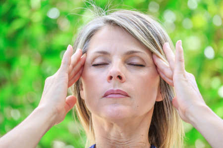 migraine: woman with intense stress and painful headache Stock Photo