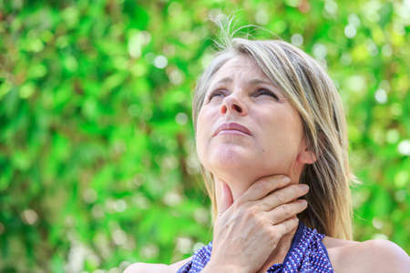 Woman with a sore throat holding her neck