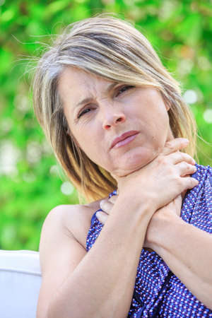 pharyngitis: Woman with a sore throat holding her neck