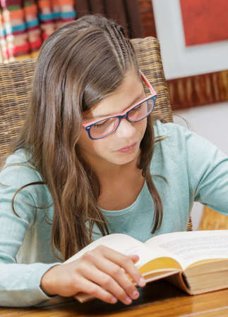 absorbed: closeup of a pretty young girl student smiling absorbed in reading a book