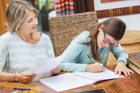 exam: pretty student girl taking tutoring courses with beautiful blond teacher