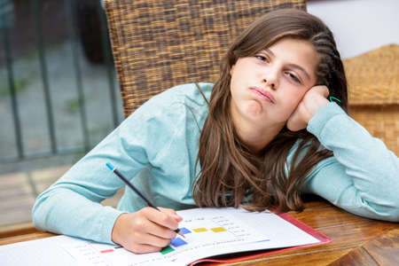disinterested: beautiful girl student doing her homework without motivation