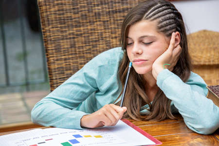 evening class: beautiful tired girl student doing her homework with concentration Stock Photo