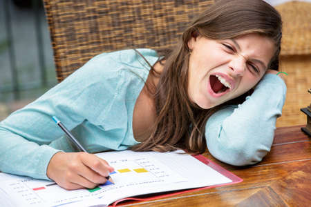 deprivation: beautiful tired girl student doing her homework while yawning
