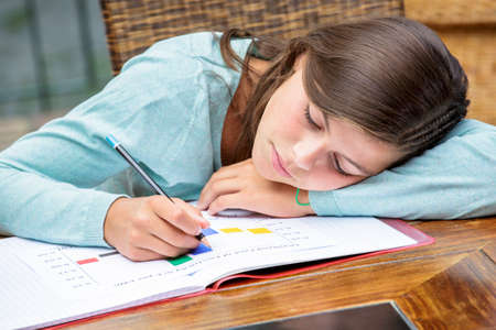 deprivation: Tired or despondent young girl do homework lying on a table Stock Photo