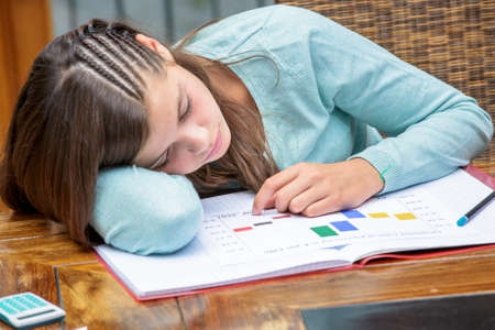 despondent: Tired or despondent young girl do homework lying on a table Stock Photo