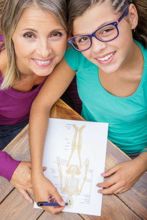 biology instruction: smiling teen girl doing its homework with her mother
