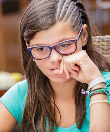 Portrait of attractive steessed teen girl trying to nail biting