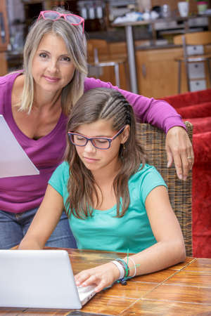 biology instruction: cute teen girl doing its homework in complicity with her mother Stock Photo
