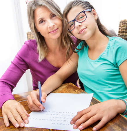 complicity: pretty teen girl doing its homework in complicity with her mother Stock Photo