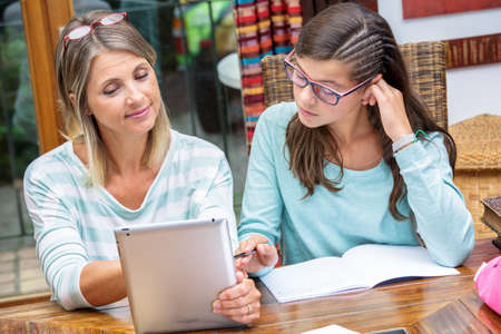 pretty student girl doing homework on tablet with beautiful middle age teacher