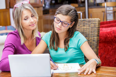 pretty teen girl doing homework with her mother