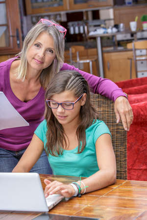 biology instruction: attractive teen girl doing its homework in complicity with her mother
