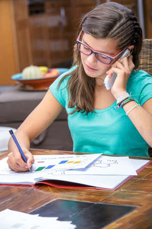 autodidact: pretty student doing his homework while talking on phone Stock Photo