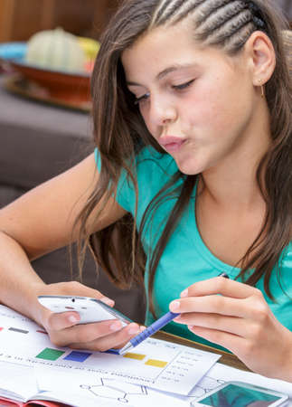 autodidact: pretty student doing homework while reading message text on her smartphone