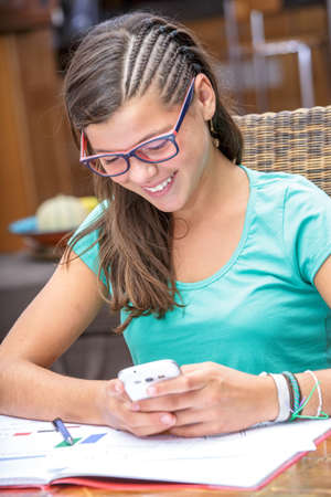 autodidact: pretty student doing homework while sending a text message