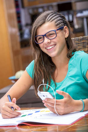 autodidact: pretty student doing homework while listening to music on her phone