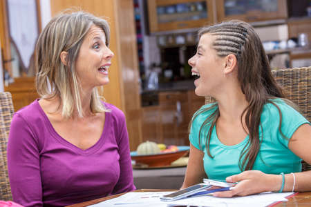 complicit�: mother and daughter sharing a moment of complicity and laughing