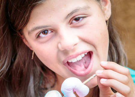 glutton: closeup of pretty young girl eating a delicious marshmallow skewer Stock Photo