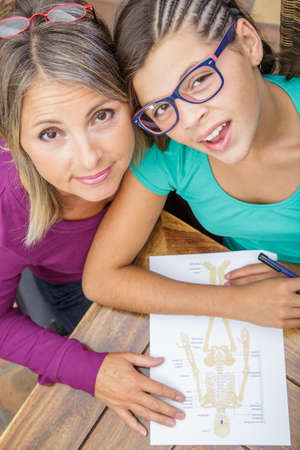 biology instruction: pretty teen girl doing its homework with middle age teacher Stock Photo