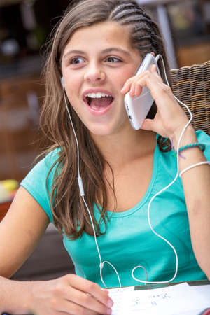 pretty student doing her homework while talking on phone Stock Photo