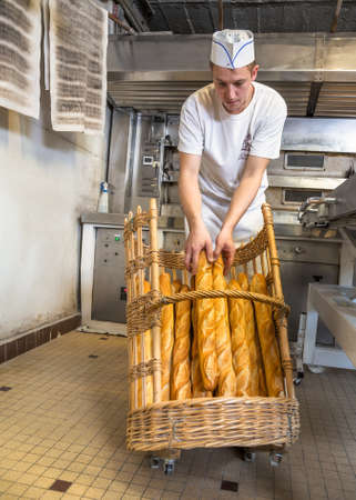 baker filing a delicious crusty baguettes in a basket