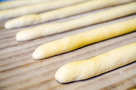 A plain baguette ready to bake on baking tray