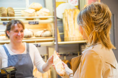 salesgirl: smiling woman with an apron selling bread to a client Stock Photo