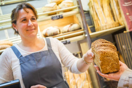 smiling woman with an apron selling bread in a bakery Stock Photo