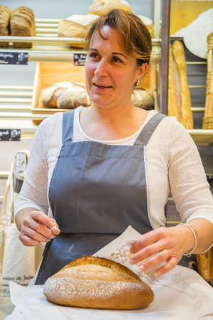 salesgirl: smiling woman with an apron selling bread in a bakery Stock Photo