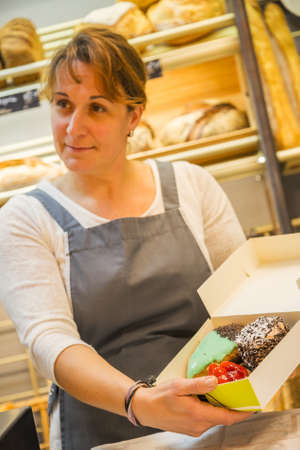 smiling woman with an apron selling pastries in the bakery Zdjęcie Seryjne