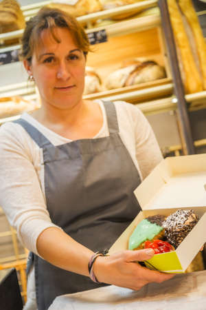 smiling woman with an apron selling pastries in the bakery Standard-Bild