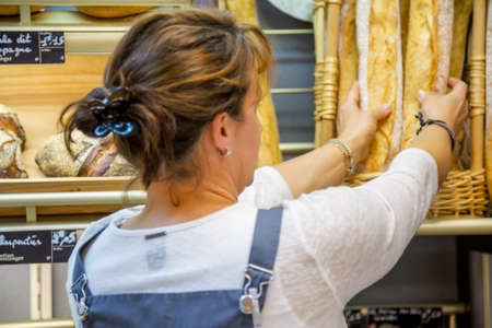 smiling woman with an apron selling bread in a bakery Standard-Bild