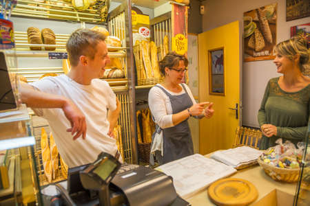 smiling woman with an apron selling bread to a client Standard-Bild