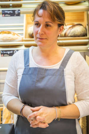 smiling woman with an apron selling bread in a bakery Archivio Fotografico