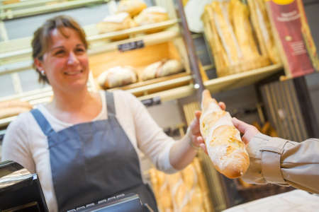 smiling woman with an apron selling bread to a client Archivio Fotografico