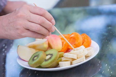 closeup of a hand that stings delicious fresh cut fruit on a plate