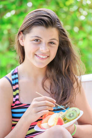 Lovely teenager with colorful clothes eating fresh fruits in a garden