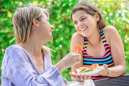 Mother and daughter eating fruits in outdoor Standard-Bild