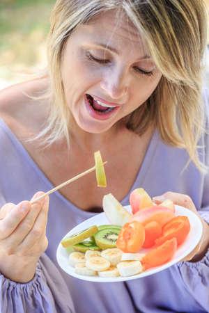 attractive blond woman eating fresh fruits Standard-Bild
