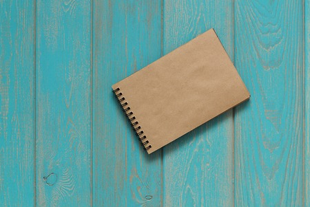 madera rústica: Note book on blue wooden desk. Top view. Foto de archivo