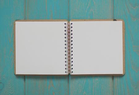 turquesa: Cuaderno en el escritorio de madera azul. Vista superior.